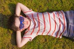 Boywithzonnebril die op het gras in de zomer zonnebaden Stock Fotografie