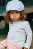 Boze éénjarigenmeisje in een gecontroleerde die GLB-zitting op speelplaats wordt beledigd Royalty-vrije Stock Fotografie