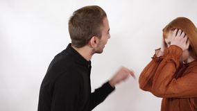 Boze agressieve mens die bij zijn mooi meisje met lang rood haar schreeuwen De vrouw sluit haar gezicht en oren, kan zij niet stock video
