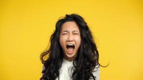 Boze Aziatische vrouw die op gele achtergrond gillen stock footage