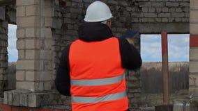 Boze civiel-ingenieur die dichtbij de bouw spreken stock video