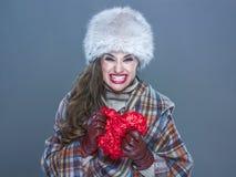 Boze die vrouw op koude blauwe achtergrond wordt geïsoleerd die rood hart verpletteren Royalty-vrije Stock Afbeelding
