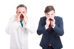 Boze dokter of arts en bedrijfsmens stock foto's