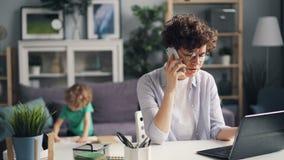 Boze freelancer die op telefoon spreken die laptop met behulp van terwijl haar zoon die in ruimte spelen stock footage
