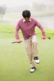 Boze golfspeler die zijn club proberen te remmen stock foto