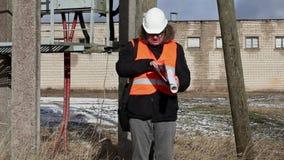 Boze Ingenieur met documentatie dichtbij powerline stock videobeelden