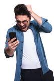 Boze jonge mens die terwijl het lezen van een tekst gillen Stock Foto