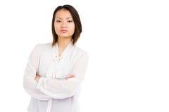 Boze jonge vrouw die zich met gekruiste wapens bevinden stock afbeelding