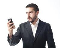 Boze jonge zakenman die mobiele telefoon kijken Stock Afbeeldingen