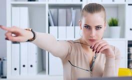 Boze Kaukasische bedrijfsvrouwenzitting bij haar bureau en het richten met vinger weg te gaan stock foto's