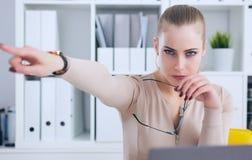 Boze Kaukasische bedrijfsvrouwenzitting bij haar bureau en het richten met vinger weg te gaan stock afbeelding