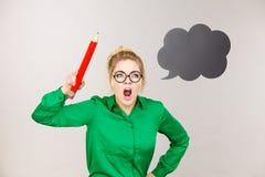 Boze leraarsvrouw die groot potlood houden royalty-vrije stock afbeelding
