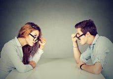 Boze man en vrouwenzitting bij lijst die elkaar met haat en afschuw bekijken Royalty-vrije Stock Foto's