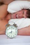 Boze mens in bed die door zijn wekker wordt geërgerda Stock Afbeeldingen