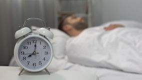 Boze mens die hoofdkussen werpen bij bellende wekker, ochtendroutine, luiheid stock video