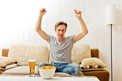 Boze mens die terwijl het letten van op sporten op TV gillen stock fotografie