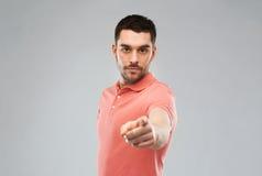Boze mens die vinger aan u over grijs richten stock foto