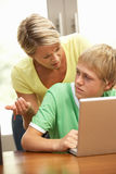 Boze Moeder en TienerZoon die Laptop thuis met behulp van royalty-vrije stock afbeelding