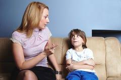 Boze moederbesprekingen aan haar zoon Stock Foto's