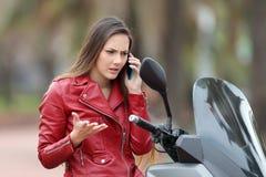 Boze motorbiker die telefoon op een motor uitnodigen stock afbeeldingen