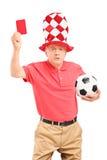 Boze rijpe voetbalventilator met bal die een rode kaart geven Stock Foto's