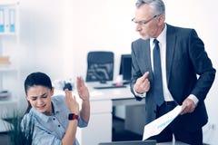 Boze rijpe werkgever die bij beklemtoonde werknemer schreeuwen stock afbeelding