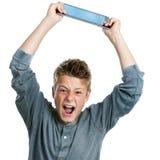 Boze tiener die tablet opheffen. Stock Fotografie