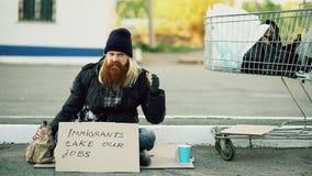 Boze verstoorde jonge dakloze mens met kartonzitting dichtbij boodschappenwagentje en drankalcohol bij koude dag wegens Royalty-vrije Stock Foto's