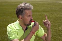 Boze voetbalscheidsrechter die een fluitje blazen stock fotografie
