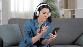 Boze vrouw die aan muziek luisteren die verpletterde telefoon met behulp van stock videobeelden