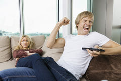 Boze vrouw die bij de vrolijke mens staren aangezien hij op TV thuis in woonkamer let Royalty-vrije Stock Foto