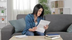 Boze vrouw die een brief thuis leest stock video