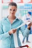 Boze vrouw die een ontvangstbewijs controleren stock foto