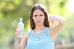 Boze vrouw die een plastic fles met neer thums houden royalty-vrije stock afbeelding