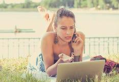 Boze vrouw die op mobiele telefoon spreken die aan laptop computer in openlucht werken stock foto