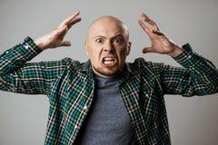 Boze woede jonge mens die over beige achtergrond schreeuwen Royalty-vrije Stock Fotografie