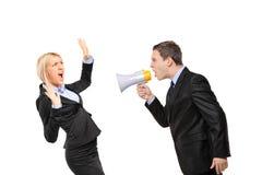 Boze zakenman die via megafoon aan een vrouw schreeuwt Stock Afbeeldingen
