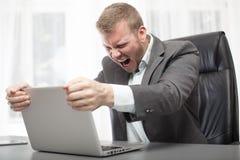 Boze zakenman die zijn laptop computer schudden