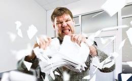 Boze zakenman tearing stapels van document royalty-vrije stock foto