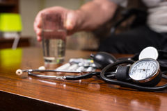 BP Apparatus on the Table with Medicines and Water Royalty Free Stock Images