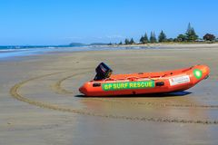 An inflatable surf rescue boat on a New Zealand beach. A BP sponsored surf lifesaving boat with a powerful outboard motor, sitting on the sand at Waihi Beach stock images