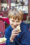 Bpy joven sonriente con pan en la mano Imagen de archivo