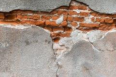 Bräcklig vägg Knäcka över väggen med röda förstörda tegelstenar arkivbild