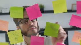 Bräde för schema för påminnelse för anmärkningspapper Affärsfolk som möter, och bruksstolpe som den noterar för att dela idé Disk stock video