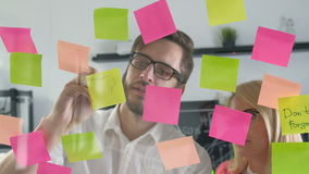 Bräde för schema för påminnelse för anmärkningspapper Affärsfolk som möter, och bruksstolpe som den noterar för att dela idé 20-t stock video