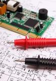 Bräde för utskrivaven strömkrets och kabel av multimeteren på diagram av elektronik royaltyfri bild