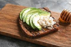 Bräde med smakligt rostat bröd på grå bakgrund, closeup royaltyfri foto