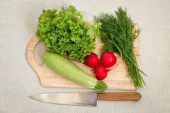 bräde som klipper olika grönsaker Arkivfoto
