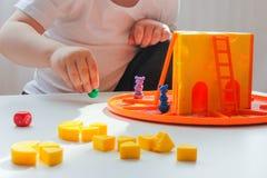 Brädeleken och begreppet av barn-enpysen spelar en lätt lek med ost och möss royaltyfri foto