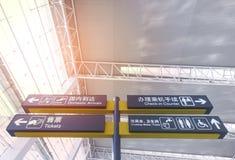 Brädet för information om den flygplatsavvikelsen & ankomsten undertecknar in kines och engelska Arkivbilder
